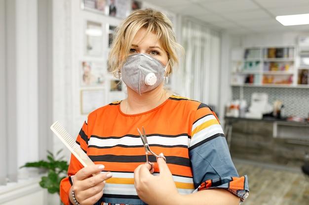 コロナウイルスの流行中にサロンで保護マスクを着用している女性の美容師