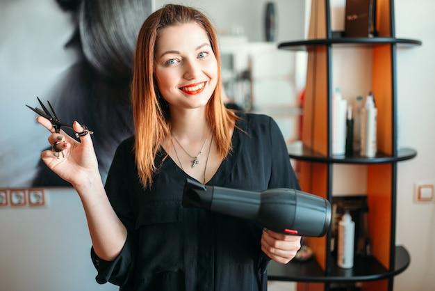 はさみとヘアドライヤーを手にした女性美容師。ビューティーサロンのヘアスタイリスト、美容院のスタイリスト