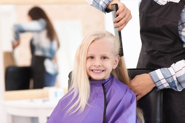 サロンで小さな女の子と一緒に働く女性の美容師、クローズアップ