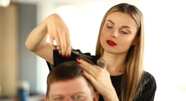 Female hairstylist cutting hair of man client. woman hairdresser holding scissors in hand. young stylist making haircut for male customer. guy getting hairdo in beauty salon. beautician styling hair