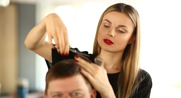 男性クライアントの髪を切る女性のヘアスタイリスト。はさみを手に持った女性美容師。男性のお客様のために散髪をする若いスタイリスト。男は美容院で髪型を取得します。エステティシャンスタイリングヘア