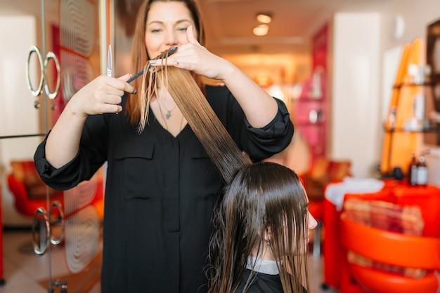 女性のヘアスタイリストが美容院で櫛を実行します。ビューティーサロンでのヘアスタイル作り