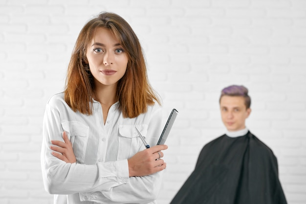 Female hairstylist standing in front of young client with toned hair.