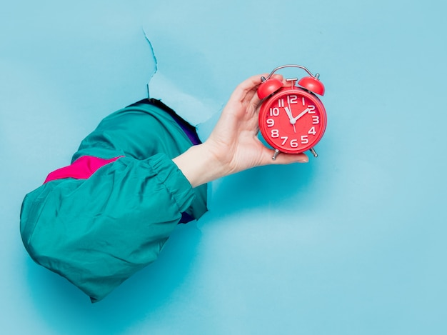 Female hand in 90s style jacket holding alarm clock