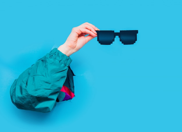 Female hand in 90s style jacket holding suglasses
