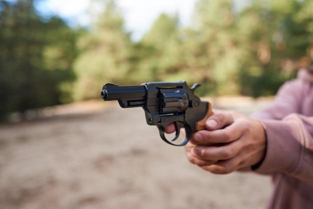 屋外でリボルバー銃を狙う女性の手。
