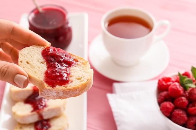 Женская рука и хлеб со сладким малиновым вареньем на столе, крупным планом