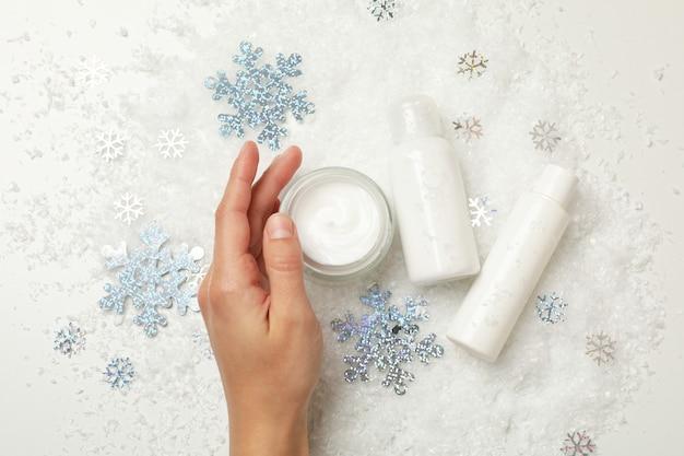 装飾的な雪の背景に女性の手と化粧品