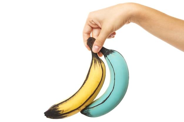 女性の手と創造的に装飾されたカラフルなバナナ