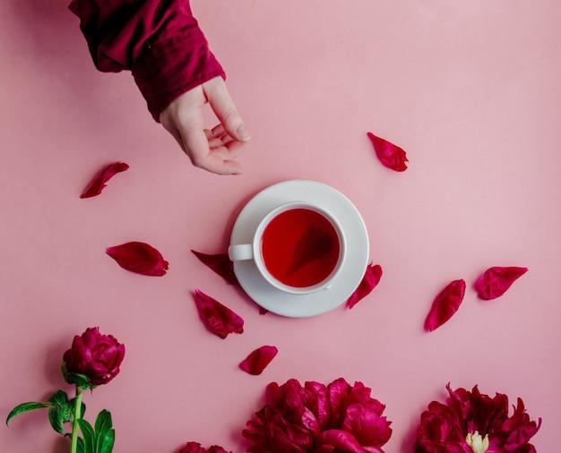 Женская рука и чашка с чаем возле пиона на розовой поверхности. вид сверху