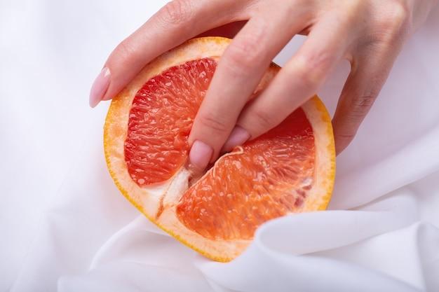女性の手とジューシーなグレープフルーツの半分。エロコンセプト