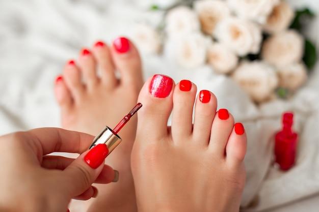 Женская рука, наносящая красный гель-лак на ногти