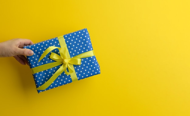 Female hand are holding a blue gift box on a yellow background, happy birthday concept, copy space
