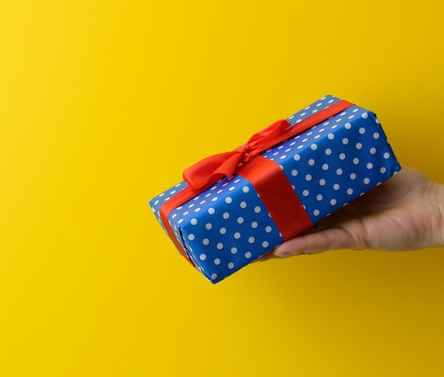 Female hand are holding a blue gift box on a yellow background, happy birthday concept