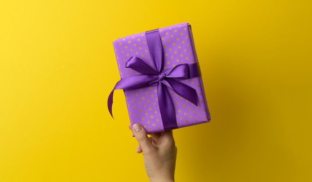 Female hand are holding a purole gift box on a yellow background, happy birthday concept