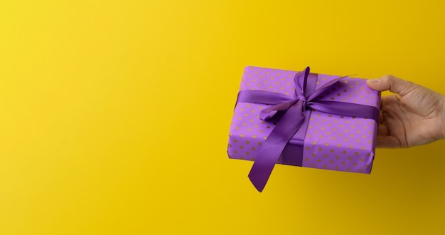 Female hand are holding a purple gift box on a yellow background, happy birthday concept