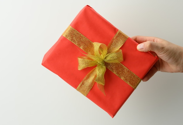 Female hand are holding a red gift box on a gray background, happy birthday concept, close up