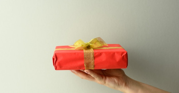 Female hand are holding a red gift box on a gray background, happy birthday concept