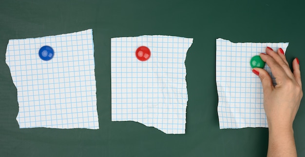 Женская рука прикрепляет чистые листы бумаги в клетке к зеленой магнитной доске, место для надписи