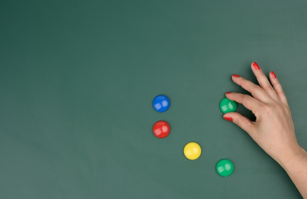Female hand attaches multi-colored magnets to a green board, place for an inscription