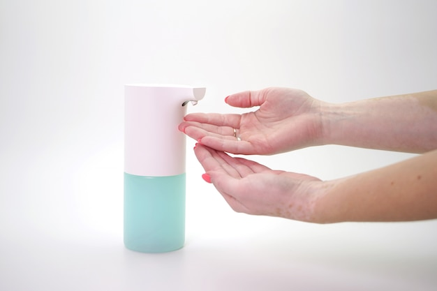Female hand and automatic dispenser, disinfectant on an isolated wall, close-up. demonstration of hand hygiene, prevention of the spread of coronavirus