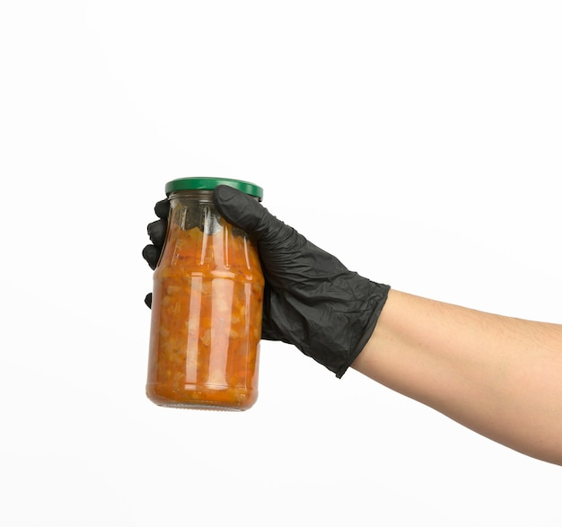 Female hand in a black glove holds a glass jar with cooked beans in tomato sauce on a white background