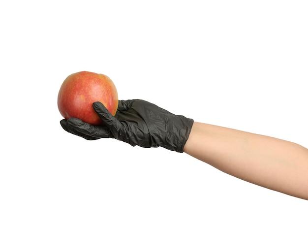 Female hand in black latex glove holds ripe red apple