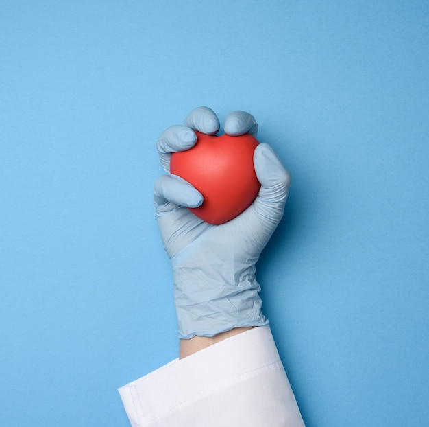 Female hand in blue latex gloves holding a red heart, donation concept, top view