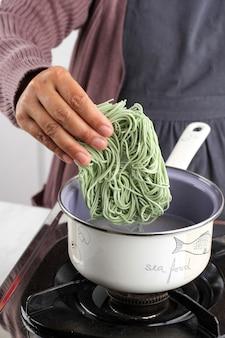 Женская рука, варящая лимонило, полезная зеленая индонезийская лапша быстрого приготовления на сковороде, добавление лапши в сковороду, домашнее задание