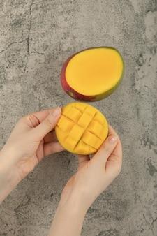 大理石の表面にエキゾチックなマンゴーの果実を壊す女性の手。
