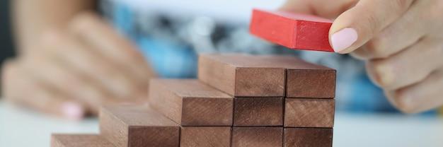 Женская рука строит лестницу из деревянных блоков сверху красный