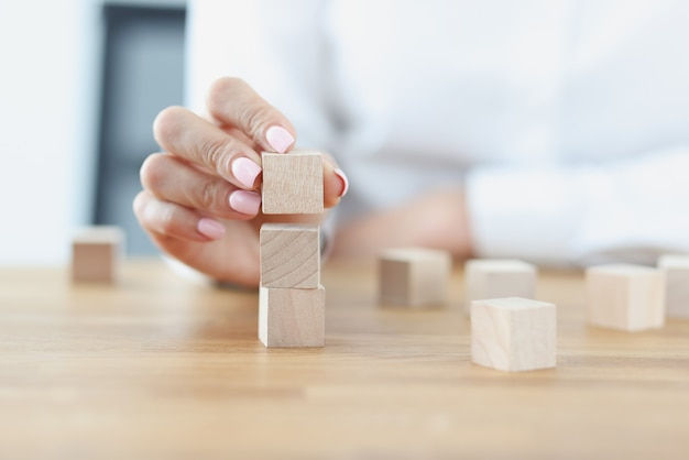 女性の手が木製の立方体から塔を建てる