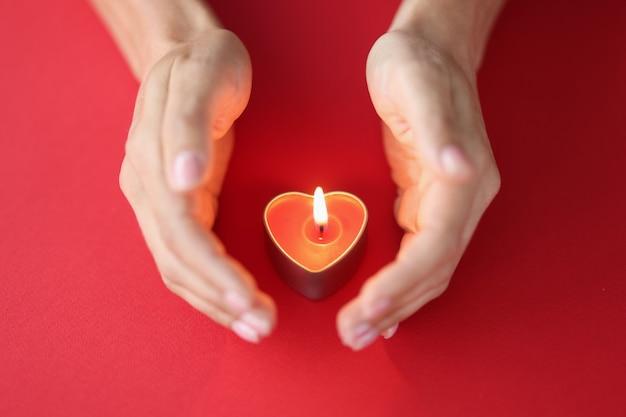 여성의 손은 빨간색 배경 촛불에 하트 모양으로 불타는 촛불을 조심스럽게 보호합니다.