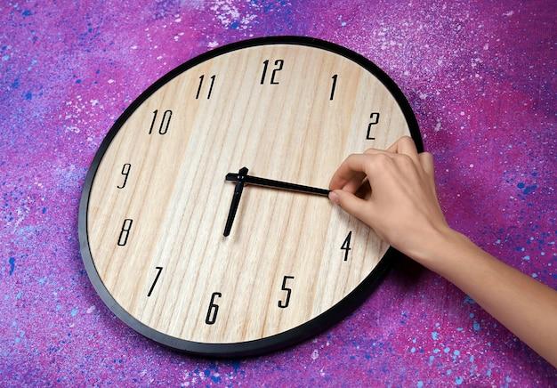 큰 벽 시계에 여성 손 변경 시간