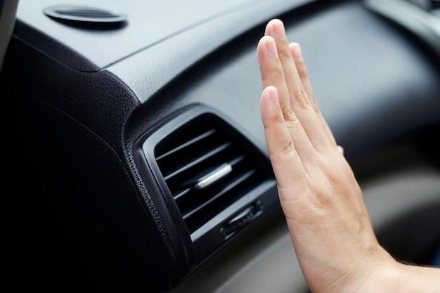 자동차의 에어컨 냉각을 확인하는 여성 손