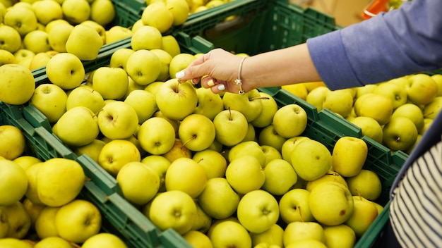 Female hand chooses green apples in the store
