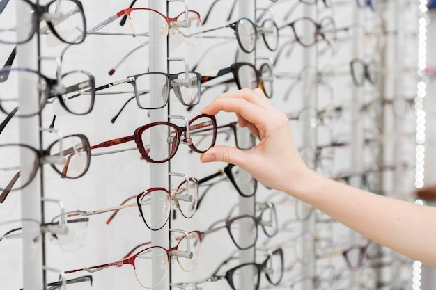 Female hand choosing eyeglasses in optics store