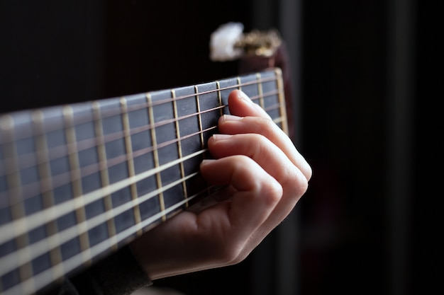 Female hand clamps a chord on an acoustic guitar.