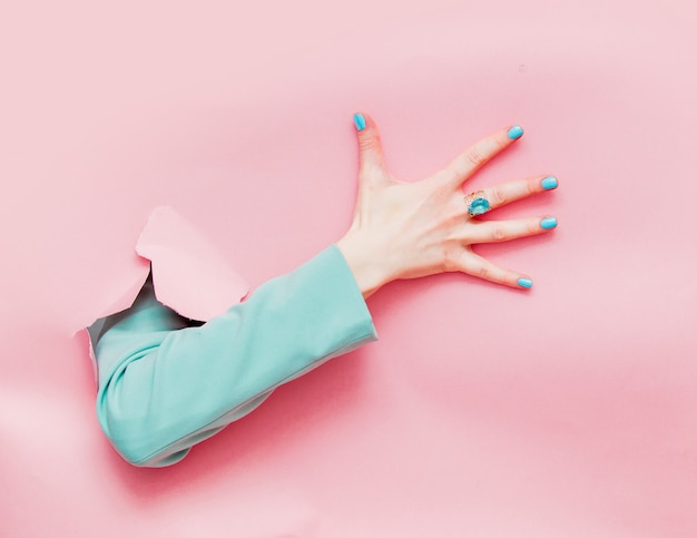 Female hand in classic blue jacket looks out from pink background