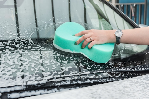 Female hand cleaning car in service with tools soap foam and water. wash auto