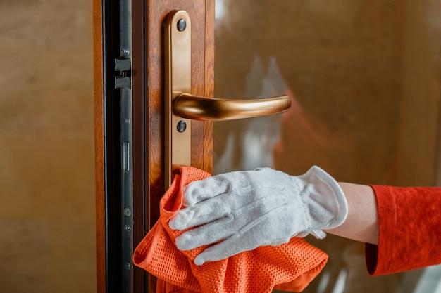 女性の手 玄関ドアの取っ手を抗菌アルコール系洗剤で洗浄。白い手袋をはめた家事労働者は、布の雑巾でドアノブを掃除します。表面の消毒における新しい通常のcovid 19コロナウイルス。