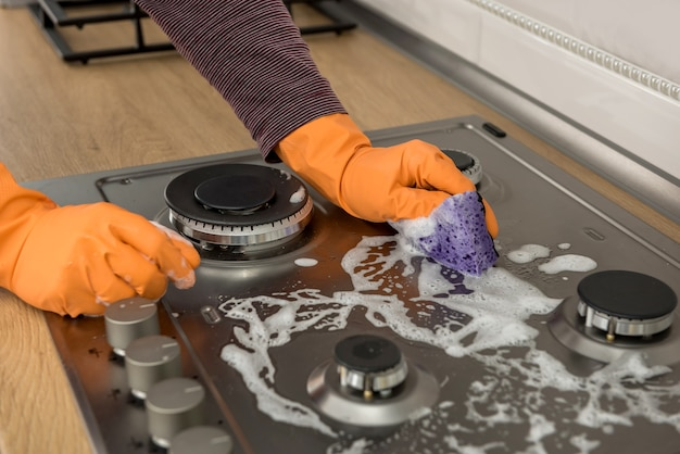Female hand cleaning gas stove with orange glove and sponge with white foam, black glass ceramic surface. domestice hygiene housework