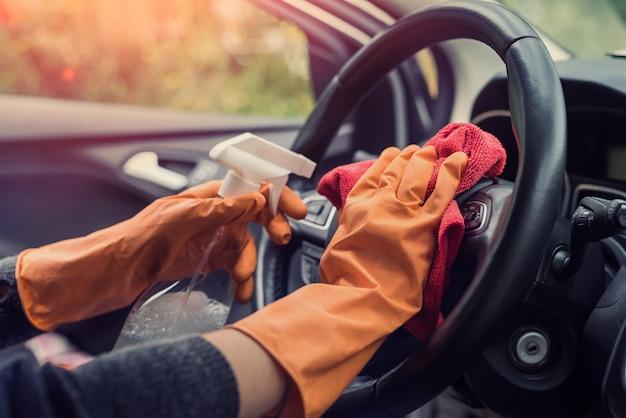 여성 손은 소독액으로 코로나바이러스와 전염병으로부터 차 내부를 청소합니다. 워시 베칠