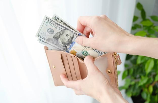 여성의 손 클로즈업은 달러가 있는 검은색 지갑을 들고 있습니다.