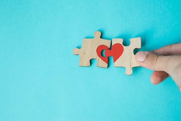 Female hand connecting puzzle with drawn red heart on blue background. love . st. valentine day. reconciliation.