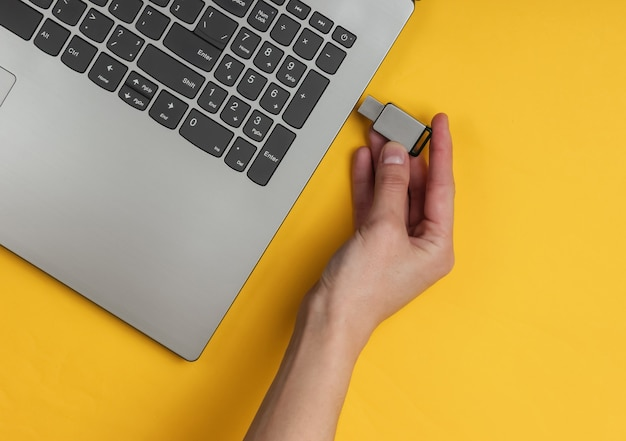 Female hand connects usb flash drive to laptop on yellow paper