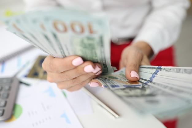 Женская рука подсчитывает наличные деньги в офисе. лот сто долларов
