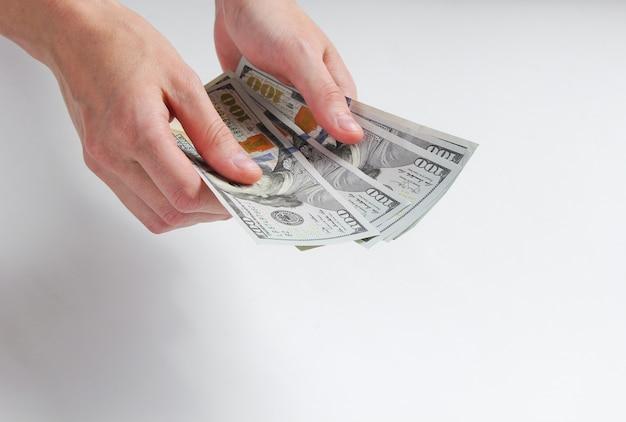 Female hand counting hundred dollar bills on white.