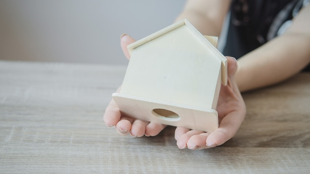 Female hand cover wooden house. house protection or financial concept