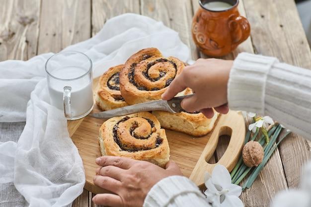 호두와 우유 한잔과 함께 오래 된 나무 테이블에 제공하는 여성 손 잼 수제 빵을 잘라